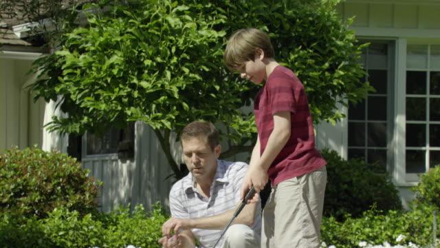 MS SHAKY ZI ZO Father teaching son (10-11) play golf in garden, Encino, California, USA