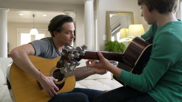 father teaching son playing guitar - gitarre stock-videos und b-roll-filmmaterial