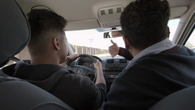 stockvideo's en b-roll-footage met father teaching son to drive and turn car - oefenen
