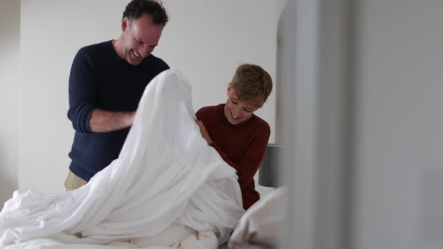 father teaching son to make a bed - sohn stock-videos und b-roll-filmmaterial