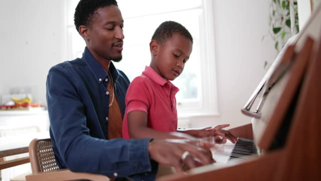 father teaching son to play the piano - kind im grundschulalter stock-videos und b-roll-filmmaterial