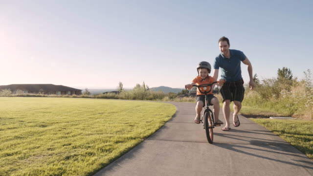 father teaching son to ride a bike - playground stock videos & royalty-free footage