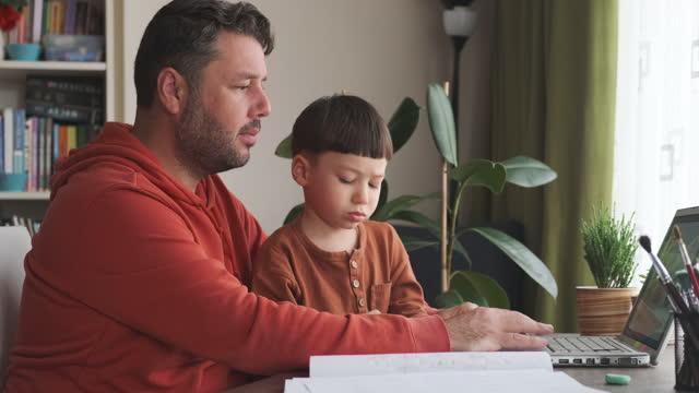 vidéos et rushes de père enseignant utilisant l'ordinateur à son fils. - son