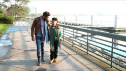 Father, teenage son walking, talking on city waterfront