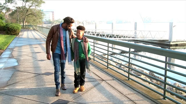 father, teenage son walking, talking on city waterfront - teenager stock videos & royalty-free footage