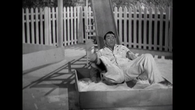 1941 Father (Cary Grant) tests a slide he's installed on deck as mother (Irene Dunne) comes outside with a visitor