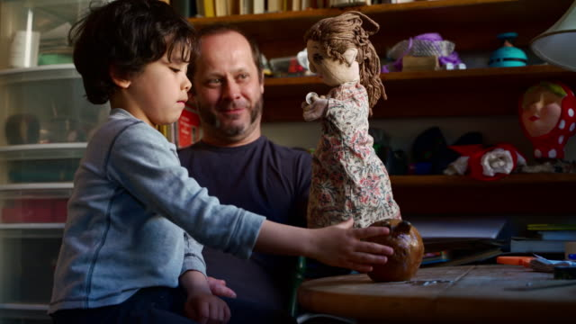 father, the puppeteer, playing with a puppet, teaches his young son to save money. father using a woman hand-puppet to take a coin from the son and to put it into the bank. - pupazzo video stock e b–roll
