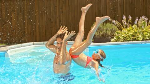 stockvideo's en b-roll-footage met slo mo vader zijn dochter van zijn schouders gooien in het zwembad - swimwear