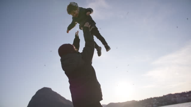 vidéos et rushes de father throwing young smiling child into the air at sunset - carrying