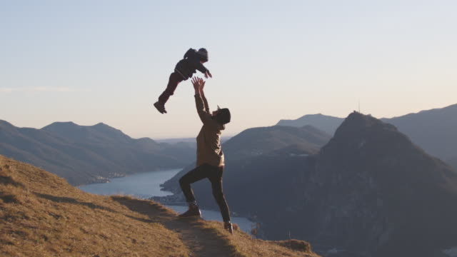 father throws young boy into the air celebrating life, view of sunset and mountains below - active lifestyle stock videos & royalty-free footage