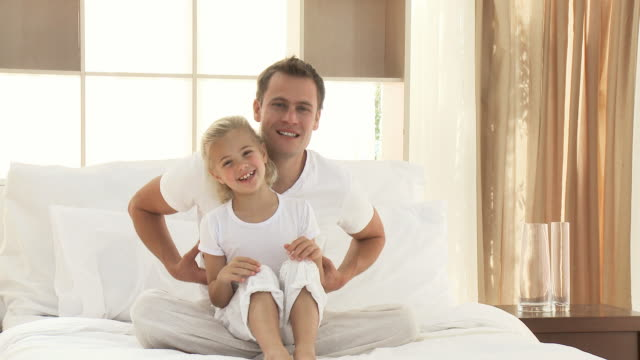 ms father tickling daughter (8-9) sitting on bed / cape town, western cape, south africa - gambe incrociate video stock e b–roll