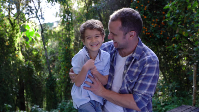 father tickling his son looking very happy and laughing - fare il solletico video stock e b–roll