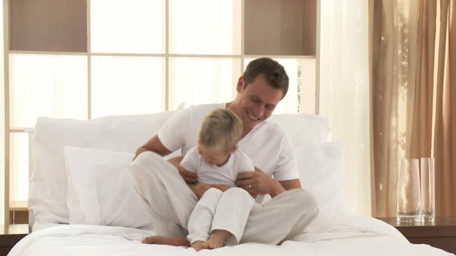 vidéos et rushes de ms father tickling son (4-5) sitting on bed / cape town, western cape, south africa - chatouiller