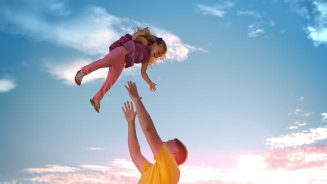 slo mo father tossing his daughter into the air in sunshine - daughter stock videos & royalty-free footage