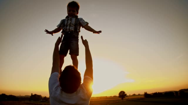 SLO MO Father tossing his son at sunset