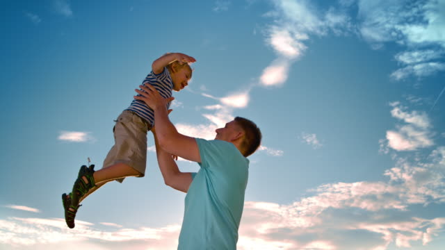 slo mo father tossing his son into the air on a sunny day outside - polo shirt stock videos & royalty-free footage