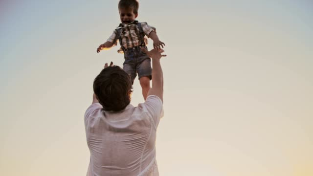 slo mo father tossing his son up in the air - trust stock videos & royalty-free footage