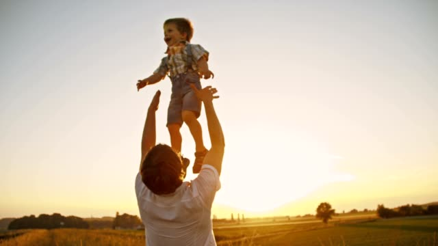 stockvideo's en b-roll-footage met slo mo father tossing his son up in the air - trust