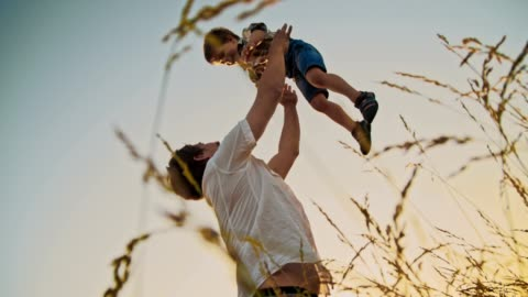 slo mo father tossing up his little son - picking up stock videos & royalty-free footage