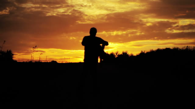 father turning around with son - sunset shot - genderblend stock videos & royalty-free footage