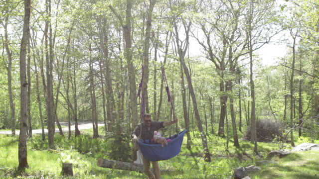 stockvideo's en b-roll-footage met father twirling daughter in boat shaped swing in a wooded yard - mid volwassen mannen