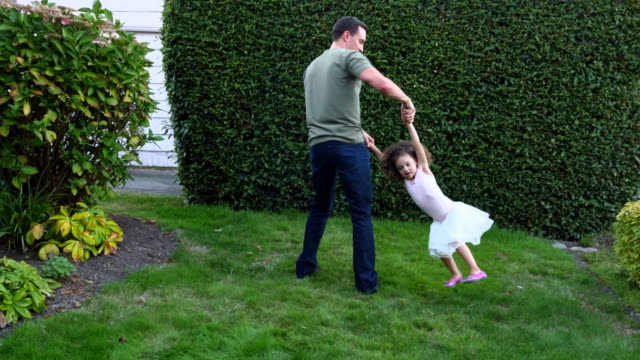 MS Father twirling young daughter in circles in yard on summer evening