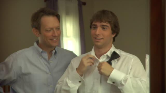 cu, father tying teenage boy's (16-17) bowtie in front of mirror, edison, new jersey, usa - schleife stock-videos und b-roll-filmmaterial