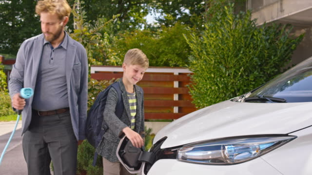 vídeos de stock e filmes b-roll de slo mo father unplugging electric car and son closing lid - sustainable resources