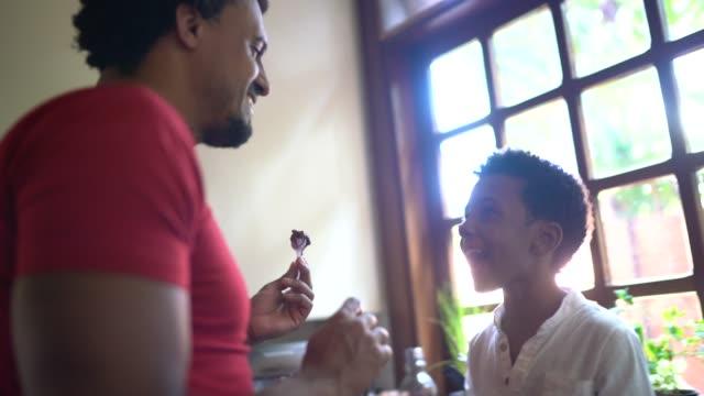 padre che usa il cioccolato per giocare con il figlio a casa - single father video stock e b–roll