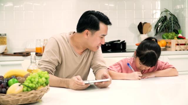 vidéos et rushes de père à l'aide de tablette numérique pour enseignement fille fait ses devoirs dans la cuisine moderne - genderblend