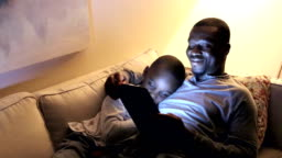 Father using digital tablet, son sleeping