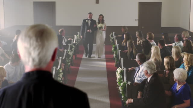 father walking bride to the preacher at the front of a chapel. - father of the bride stock videos and b-roll footage