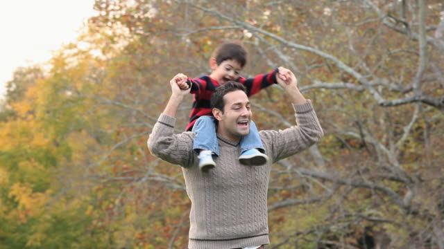 ms pan father walking, carrying son (2-3) on shoulders in back yard / richmond, virginia, usa - 肩に乗せる点の映像素材/bロール