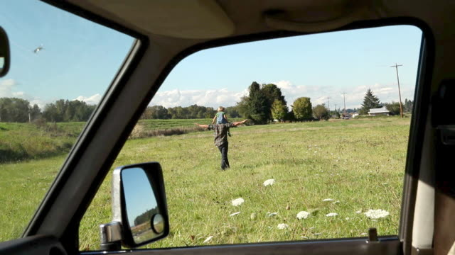 Father walking in field with son on shoulders in a field, viewed from inside a car