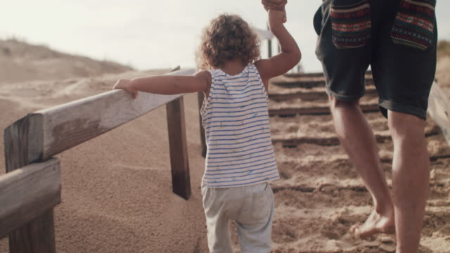 stockvideo's en b-roll-footage met father walking up sand dune with baby boy, holding hands - trap buiten