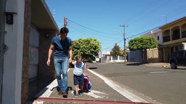 father walking with his son go back to school. down sindrome. - son stock videos & royalty-free footage
