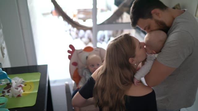 vater zu fuß mit neugeborenen und ankunft in der küche, wo mutter fütterung kleinkind - parent stock-videos und b-roll-filmmaterial