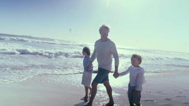 Father walking with sons on beach