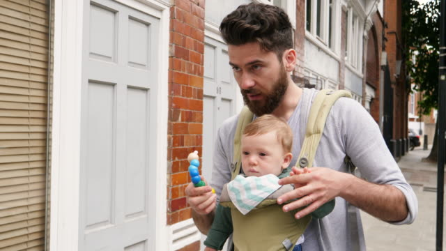 Father walks with son in baby carrier down urban road.