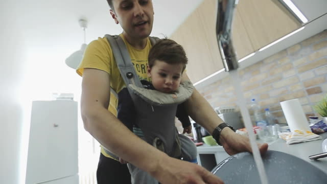 father washing dishes with a baby in a baby carrier - chores stock videos & royalty-free footage