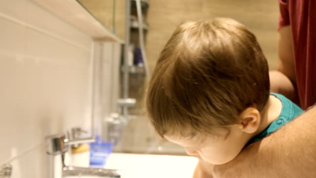 vidéos et rushes de père lavant des mains de fils dans la salle de bains - salle de bain