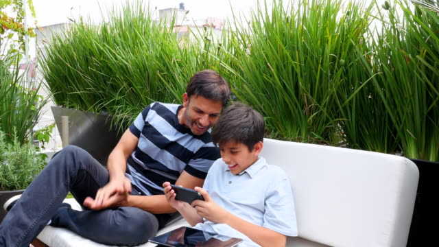 vídeos de stock e filmes b-roll de ms father watching son play game on smartphone while sitting together on patio - papa