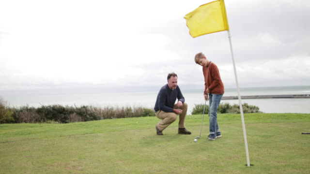 vidéos et rushes de father watching son play golf - golf