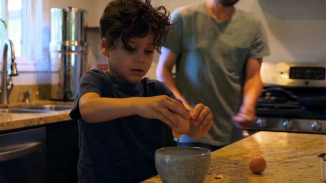 ms father watching young son crack egg into bowl in kitchen while making breakfast - prima colazione video stock e b–roll