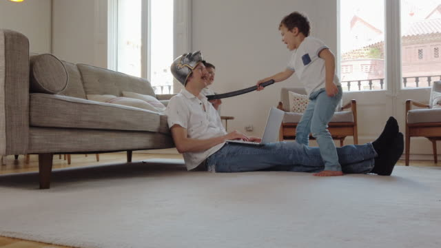 vídeos de stock e filmes b-roll de father wearing a helmet trying to work from home - travessura