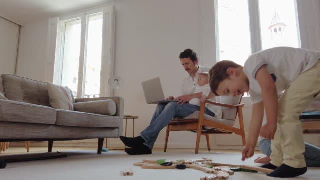vídeos y material grabado en eventos de stock de padre usando un casco tratando de trabajar desde casa - adversidad
