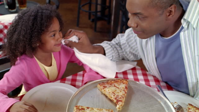 father wiping daughter's mouth with napkin at pizza restaurant / daughter taking slice of pizza off tray - napkin stock videos & royalty-free footage