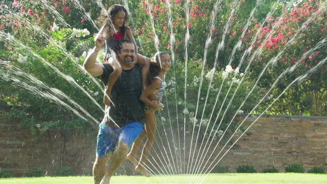 vídeos de stock, filmes e b-roll de father with 2 daughters playing in a water sprinkler - aspersor