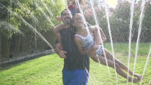 Father with 2 Daughters Playing in a Water Sprinkler
