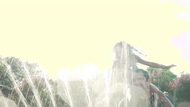 vídeos de stock e filmes b-roll de father with 2 daughters playing in a water sprinkler - carregar uma pessoa nos ombros